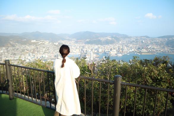 稲佐山山頂から見た長崎市街地(景色を見る女性)